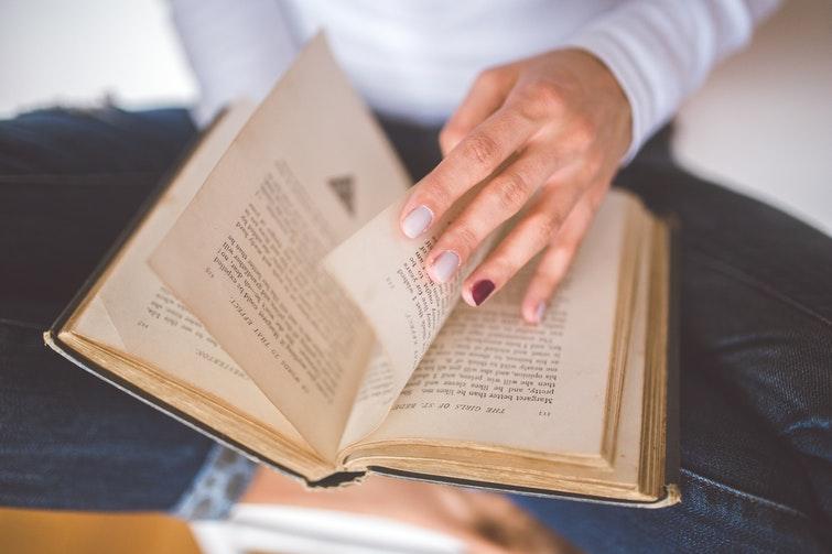 Person bläddrar sida i bok